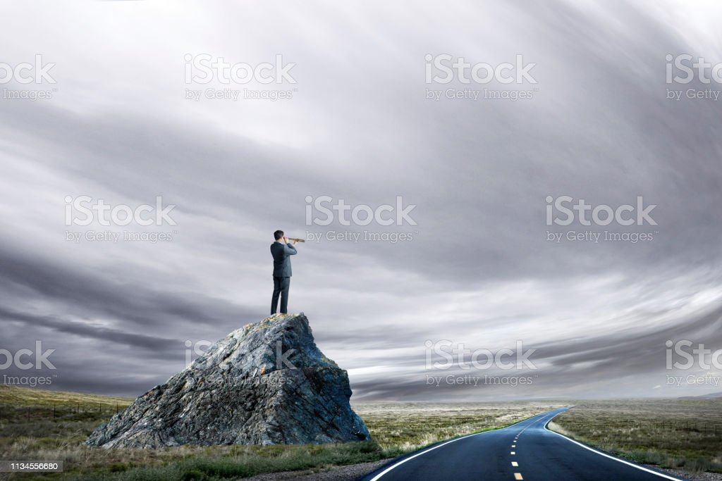 Businessman Looks Through Spyglass From A Perch On Large Rock stock photo