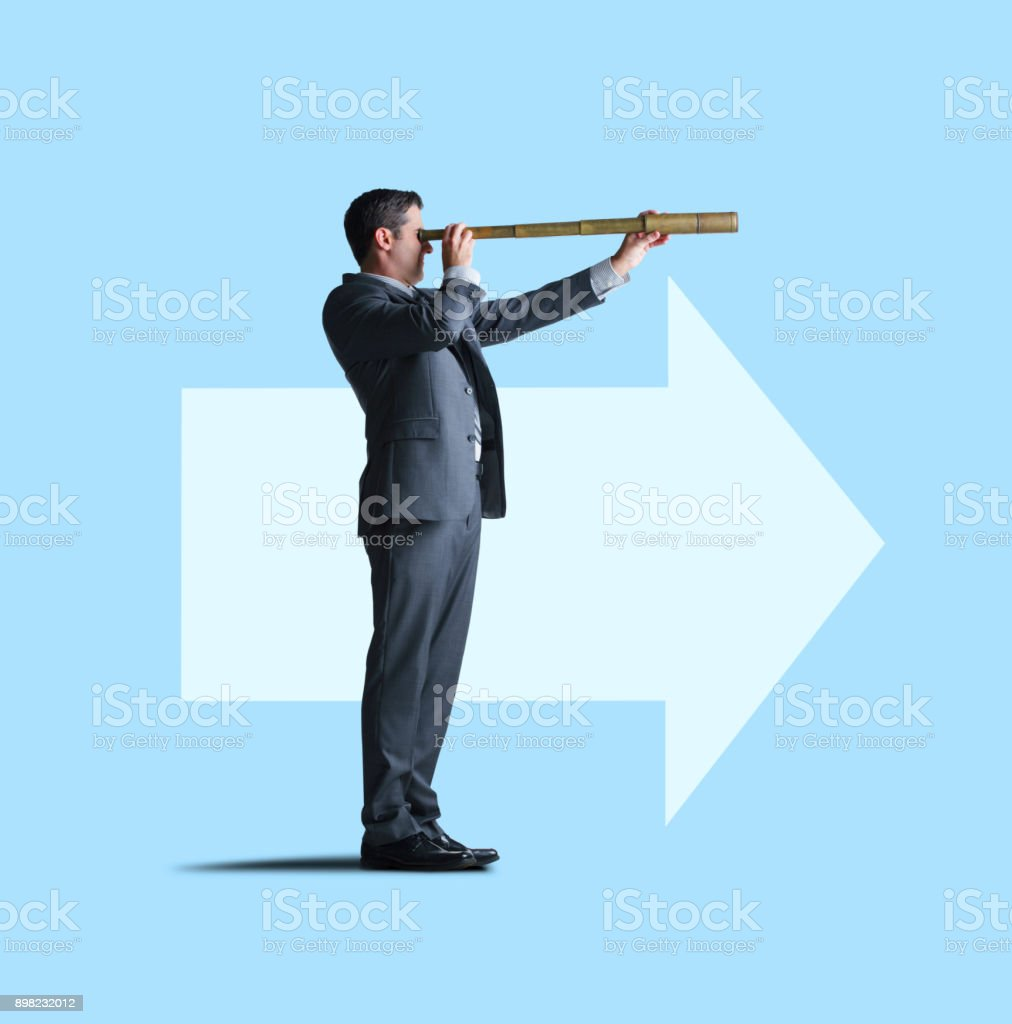 Businessman Looks Through Spyglass In Direction Of Arrow stock photo