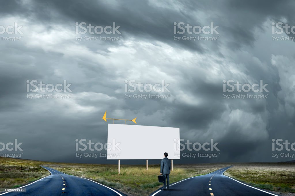 Businessman Looks Up At Blank Billboard At Fork In The Road stock photo