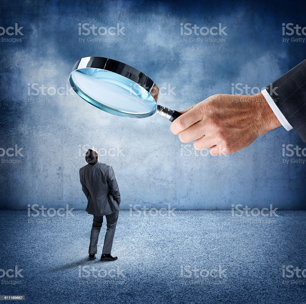 Businessman Looks Up At Businessman Holding Large Magnifying Glass stock photo