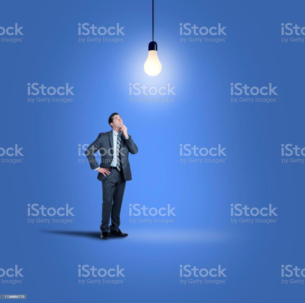 Businessman Looks Up At Lightbulb stock photo