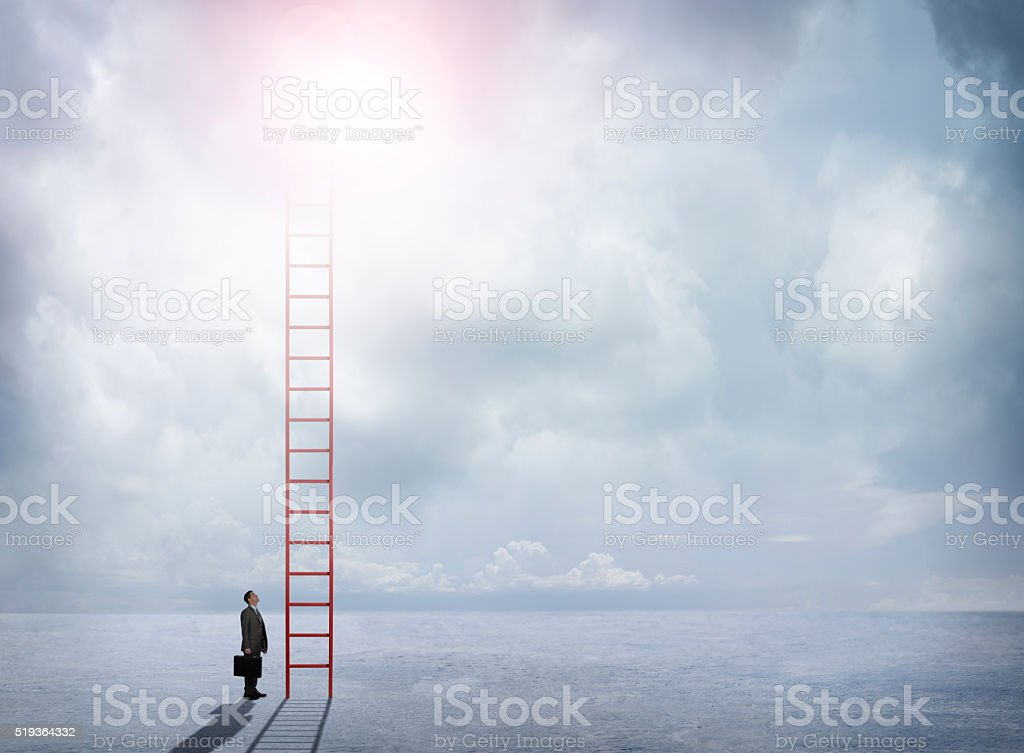 Businessman Looks Up At Red Ladder Extending Into The Clouds stock photo