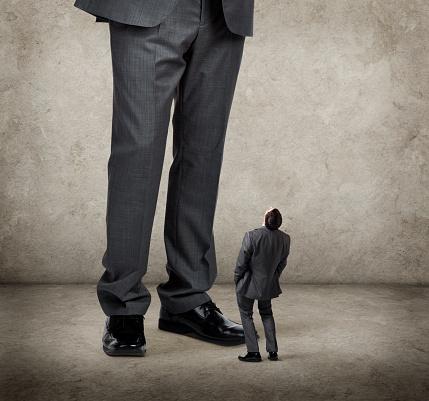 Businessman Looks Up Towards Much Larger Businessman