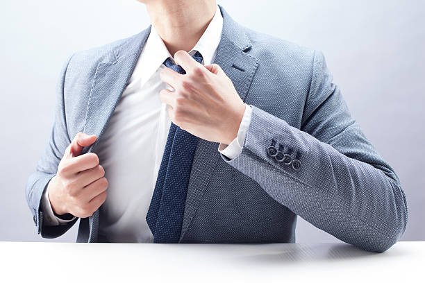 Businessman Loosening Necktie Businessman loosening necktie at the desk. undressing stock pictures, royalty-free photos & images