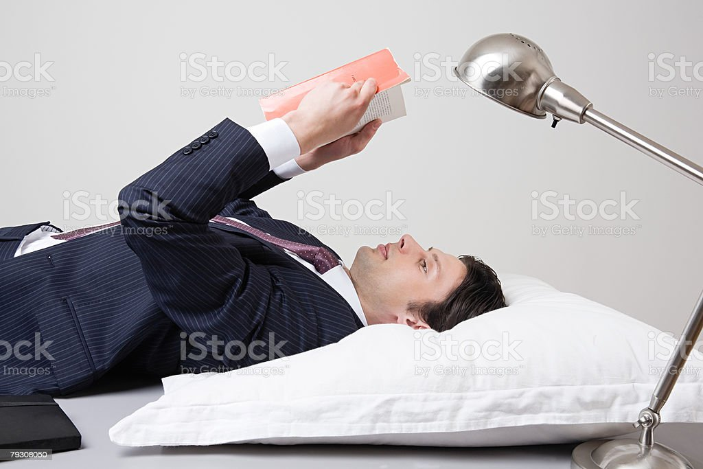 Businessman lying down and reading 免版稅 stock photo