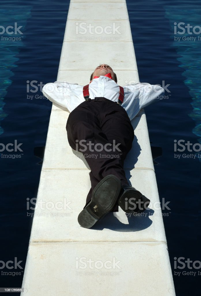 Businessman Lying on Cement Divider Between Swimming Pools royalty-free stock photo