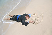 Young man businessman castaway sleeping at the keyboard of his sand computer on empty beach