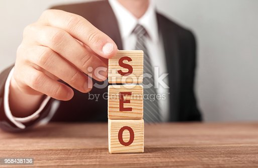 istock Businessman made word SEO with wood building blocks. 958438136