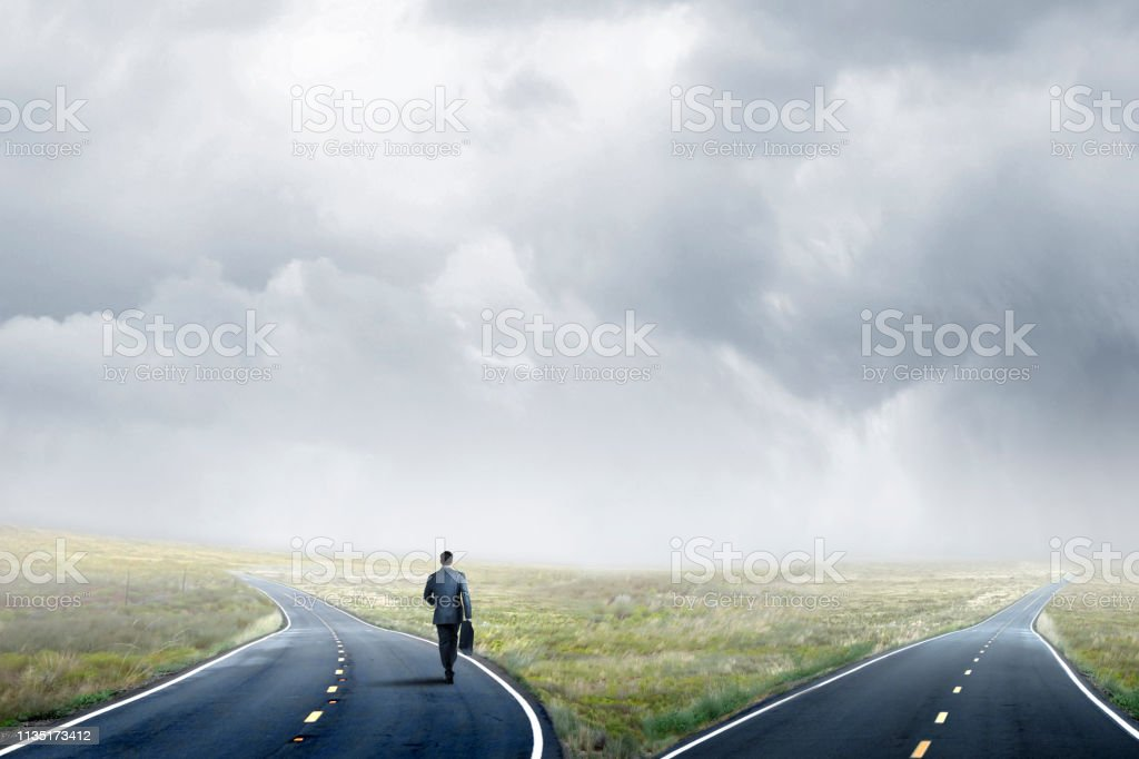 Businessman Makes A Decision At A Fork In The Road stock photo