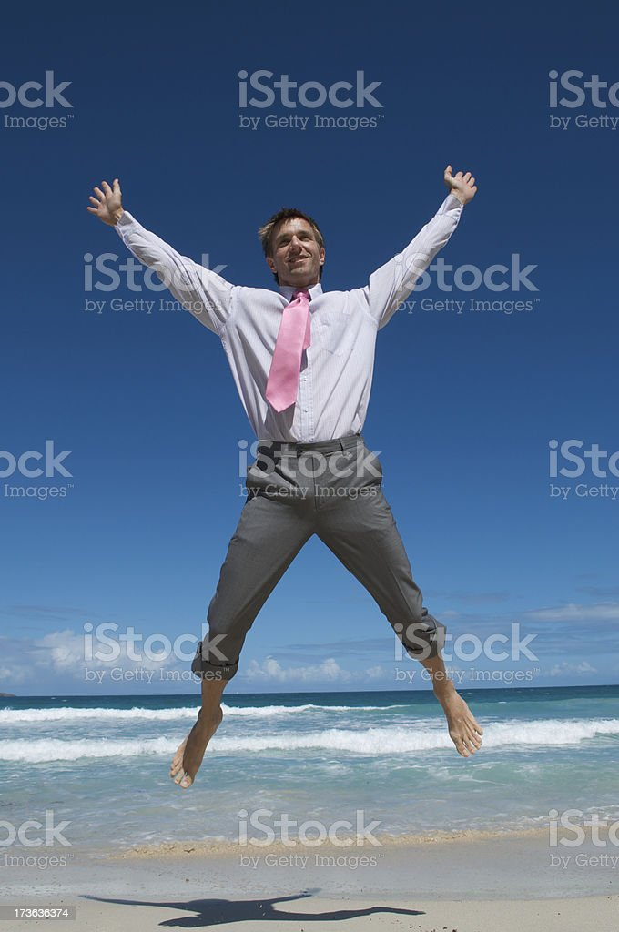 Businessman Makes Leap of Excitement on Tropical Beach stock photo