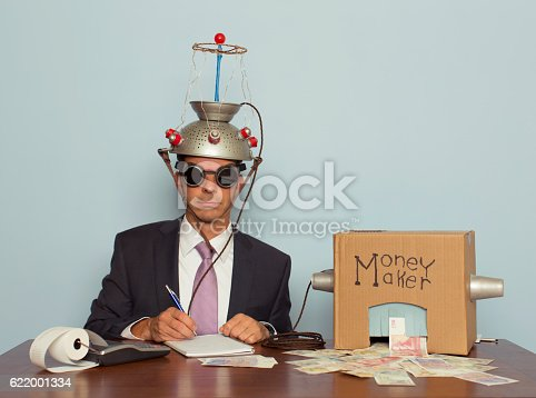 A businessman sitting at a desk records the amount of British Pound Sterling his machine makes from the ideas in his head.  He is dressed in a suit and purple tie, glasses, and a mind reading helmet on his head. Bling.