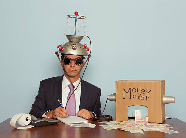 Businessman Makes Money with Helmet and Money Machine A businessman sitting at a desk records the amount of British Pound Sterling his machine makes from the ideas in his head.  He is dressed in a suit and purple tie, glasses, and a mind reading helmet on his head. Bling. bringing home the bacon stock pictures, royalty-free photos & images