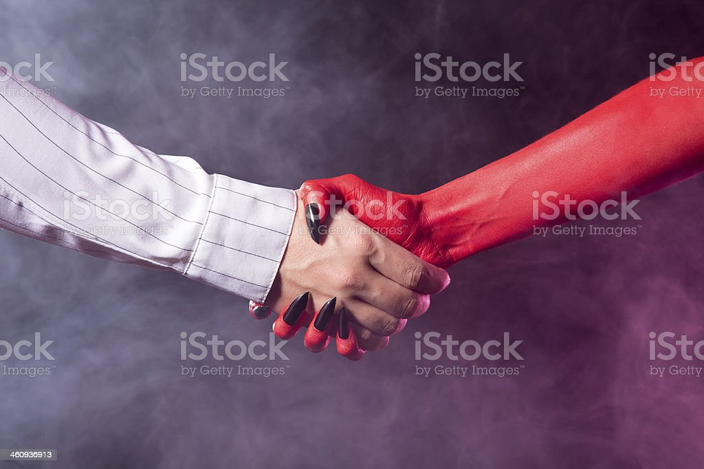 Businessman making a deal with devil stock photo