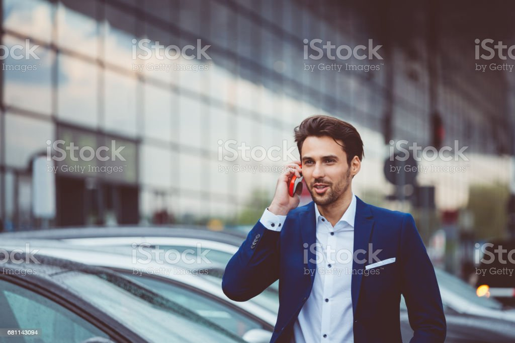 Businessman making a phone call at airport parking lot stock photo