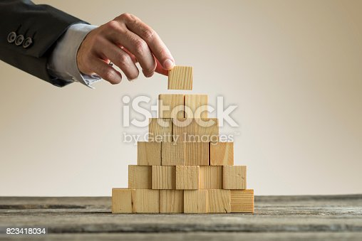 istock Businessman making a pyramid with empty wooden cubes 823418034