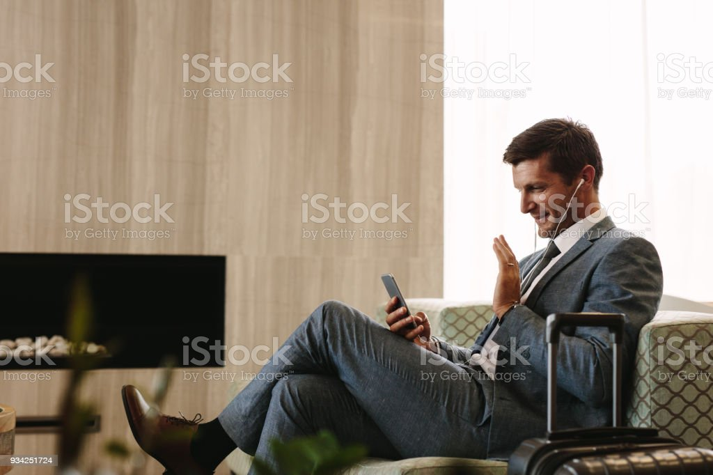 Businessman making a video call while waiting for his flight stock photo