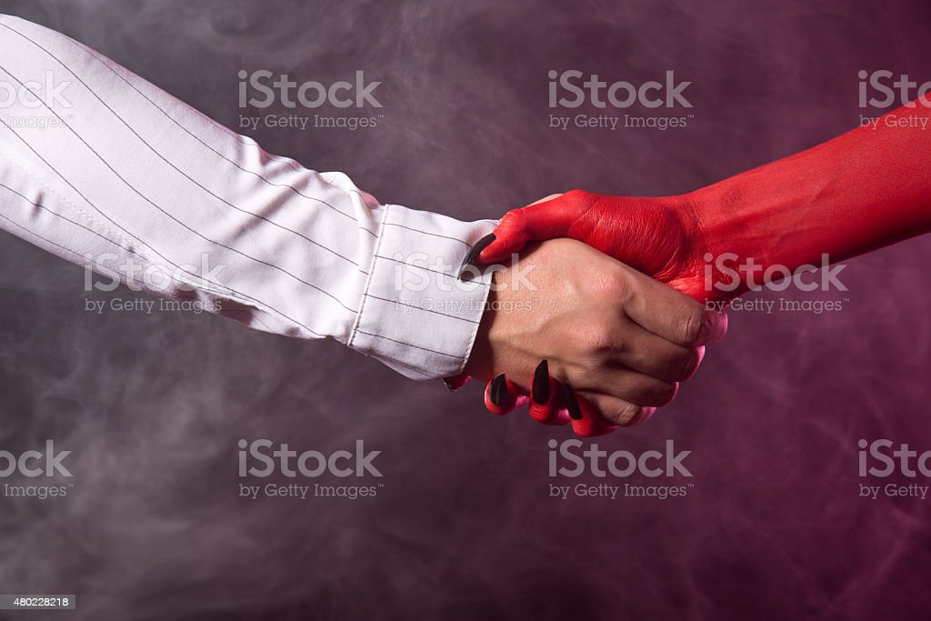 Businessman making an agreement with devil stock photo