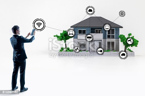 istock businessman making connection to smart house with tablet PC 810397182