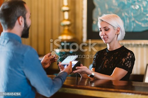 A businessman is making a contactless payment at a hotel reception.