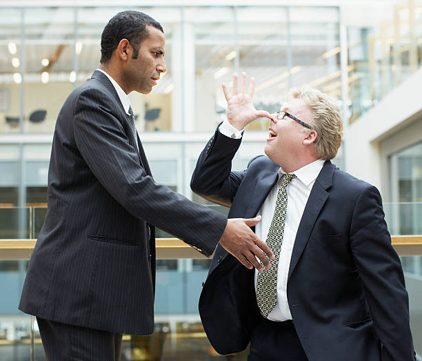 businessman making face at co-worker - rudeness stock pictures, royalty-free photos & images