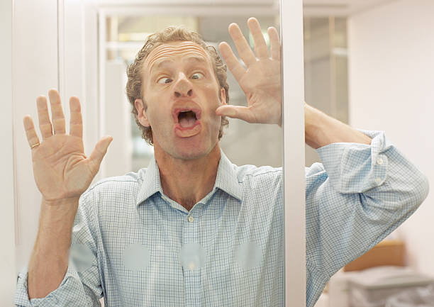 Businessman making face on glass wall stock photo