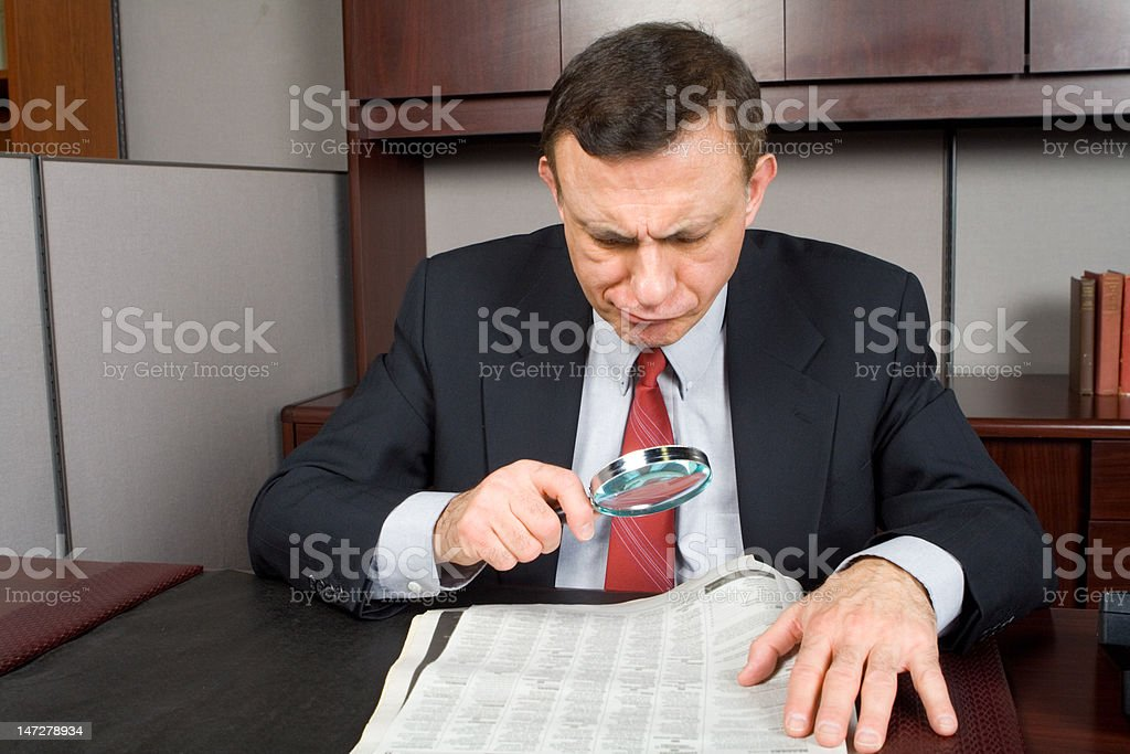 Businessman making face while looking at  newspaper royalty-free stock photo