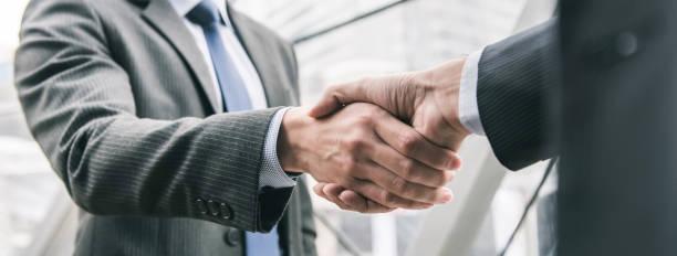 Businessman making handshake with partner stock photo
