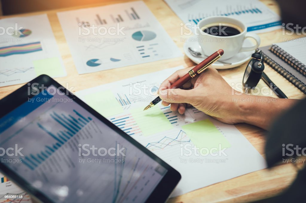 Businessman making note on sticky with looking graph in tablet. - Royalty-free Adult Stock Photo