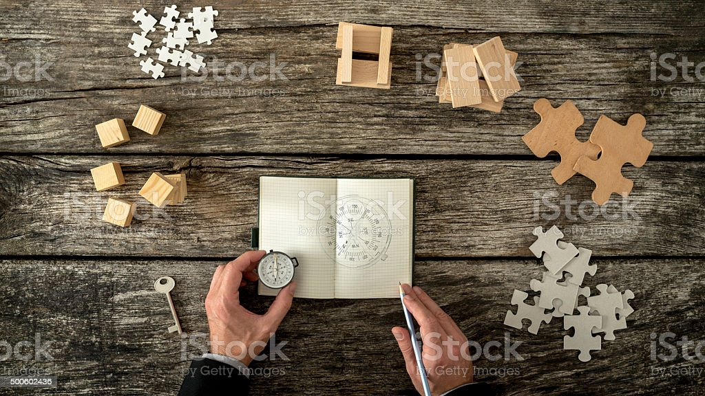 Businessman making plan and business strategy decisions as he sk Businessman making plan and business strategy decisions as he sketches a compass he is holding into his notebook. Various cubes, pegs, puzzles and a key lying on his wooden office desk, top view. 2015 Stock Photo