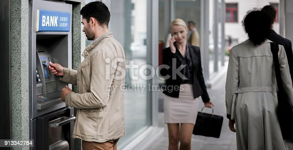 istock Businessman making withdrawal from ATM machine 913342784