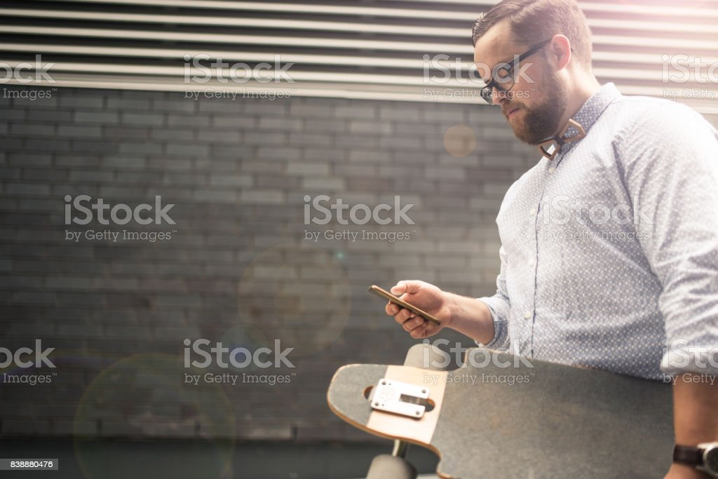 Businessman managing his business while skateboarding stock photo