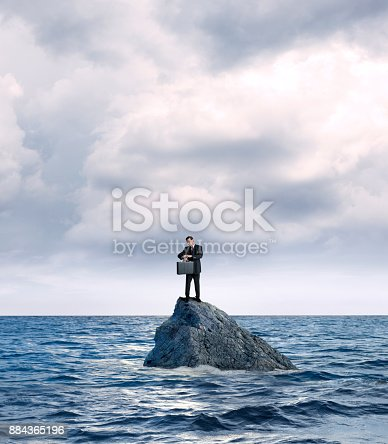 A businessman holding a briefcase stands on a rock in the middle of the ocean as he checks his wristwatch for the time.