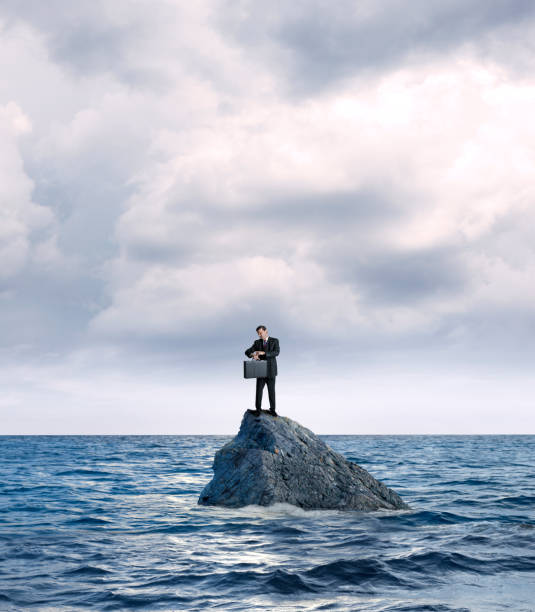 Businessman Marooned On Rock In Ocean Checks His Watch A businessman holding a briefcase stands on a rock in the middle of the ocean as he checks his wristwatch for the time. aground stock pictures, royalty-free photos & images