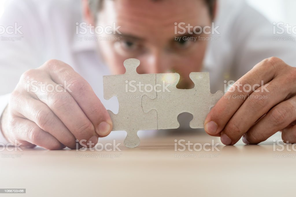 Businessman merging together two matching puzzle pieces stock photo