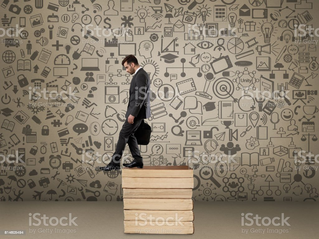 Businessman moving down stack of books stock photo