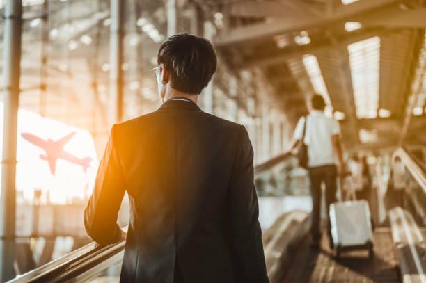 zakenman verhuist naar terminal gate voor check-in boarding met bagage op de luchthaven naar zakenreis. - zakenreis stockfoto's en -beelden