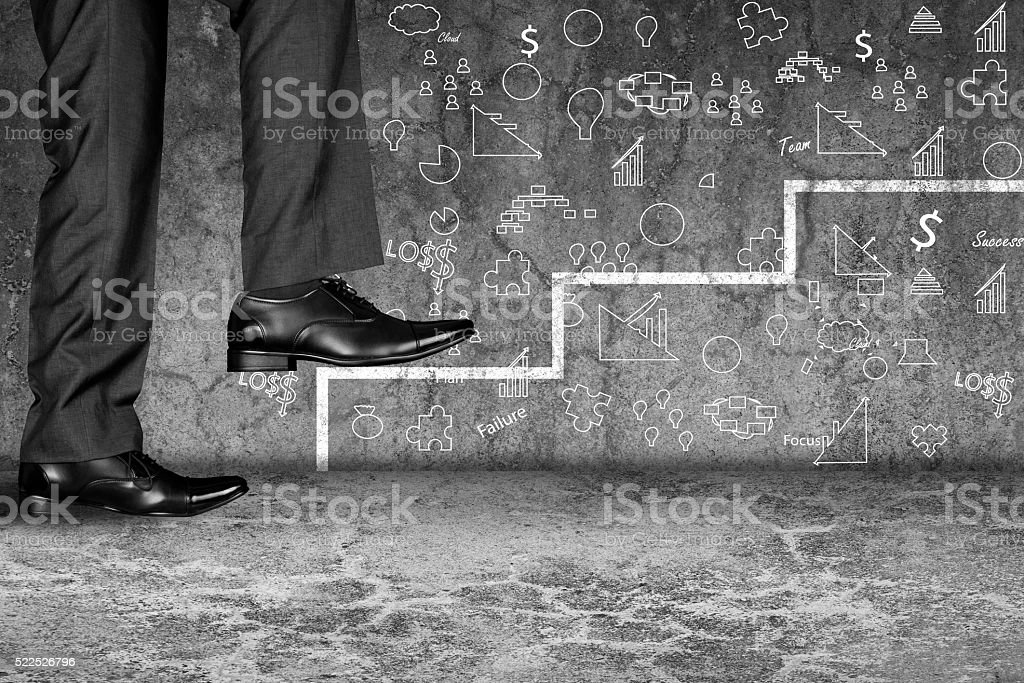Businessman moving up on first step against dirty wall stock photo
