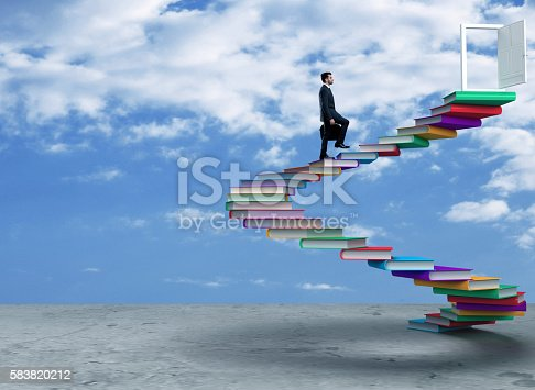 istock Businessman moving up on steps to achieve success 583820212
