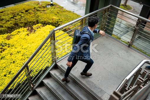 Good-looking businessman hurrying up to work, moving upstairs, checking the time on his wristwatch