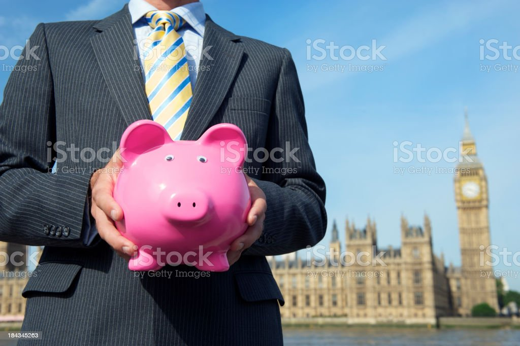 Businessman MP Holding Piggy Bank before Houses of Parliament stock photo