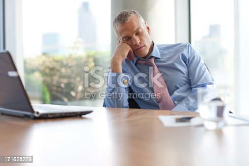 istock Businessman napping at desk in office 171628279