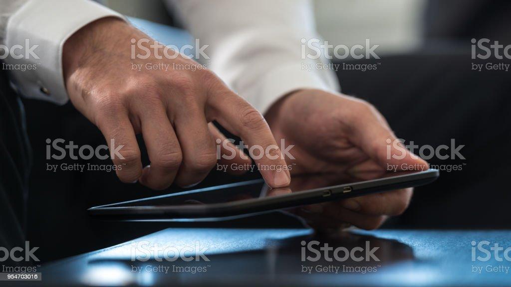 Geschäftsmann, einen Tablet-Computer aktivieren den Touchscreen mit dem Finger navigieren – Foto