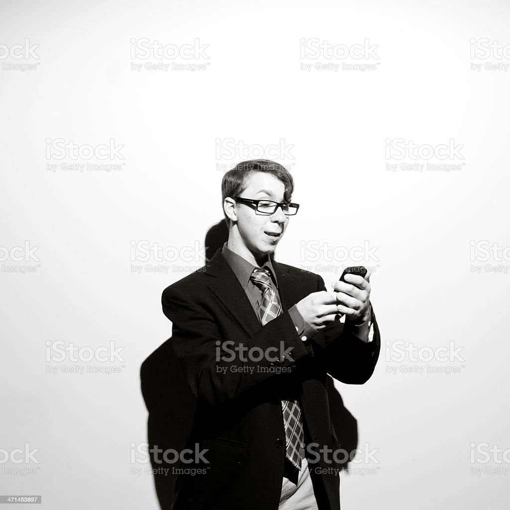 Businessman Next To White Wall Uses his Smart Phone royalty-free stock photo