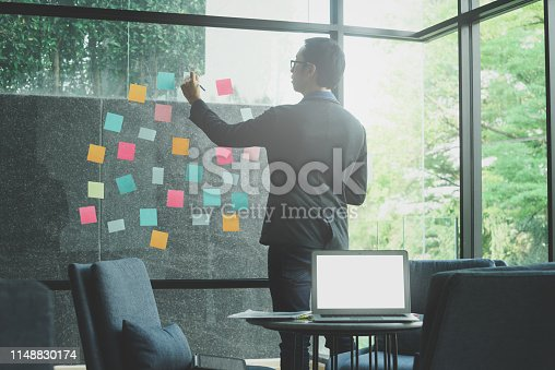 Businessman note down on sticky note and place on glass wall for team meeting collaboration