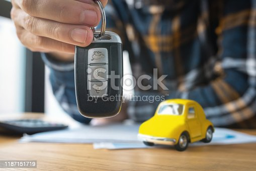 936987338 istock photo Businessman offering a car key with contract. Car rental 1187151719
