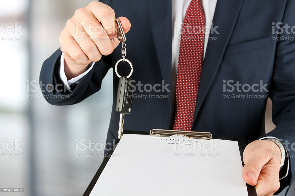 Businessman offering a car key with contract. Car rental stock photo