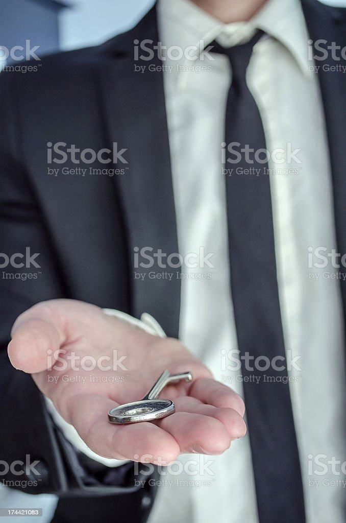 Businessman offering a key royalty-free stock photo