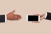 Businessman offering blank smartphone to partner