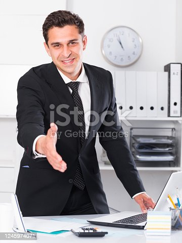 Businessman stretching open hand offering handshake and inviting to cooperation