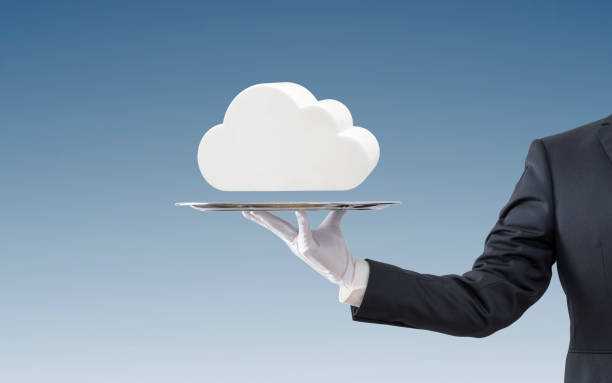 Businessman offering white cloud on silver tray over blue background stock photo